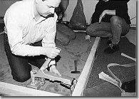Einsatz des Hebelspanners: Der Abstand zwischen Wand und Spannkopf sollte ausreichen, um den Teppichboden mit einer Spachtel auf die Nagelspitze zu drücken oder anzureiben, während man den Hebelarm langsam zurückkommen läßt