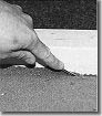 Letzter Schritt: Die überstehenden 5 mm werden abschließend mit Hilfe einer Ahle in die Fugen zwischen Nagelleiste und Wand eingedrückt